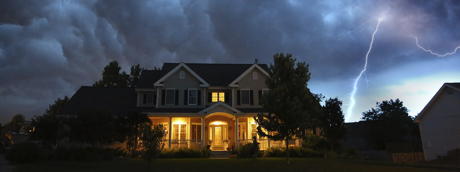Lightning strikes behind a home