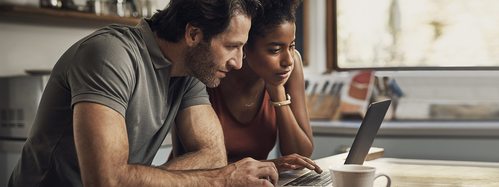 A couple looks at a laptop screen