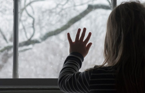 Girl looking out a window on snow-covered trees