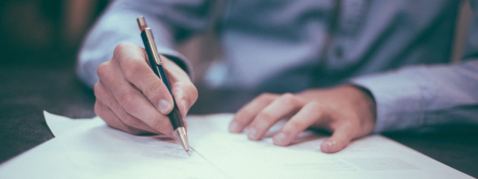 Man writing on paper with a pen