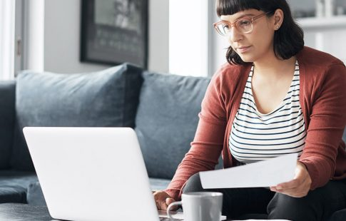 Woman looking at laptop on coffee table