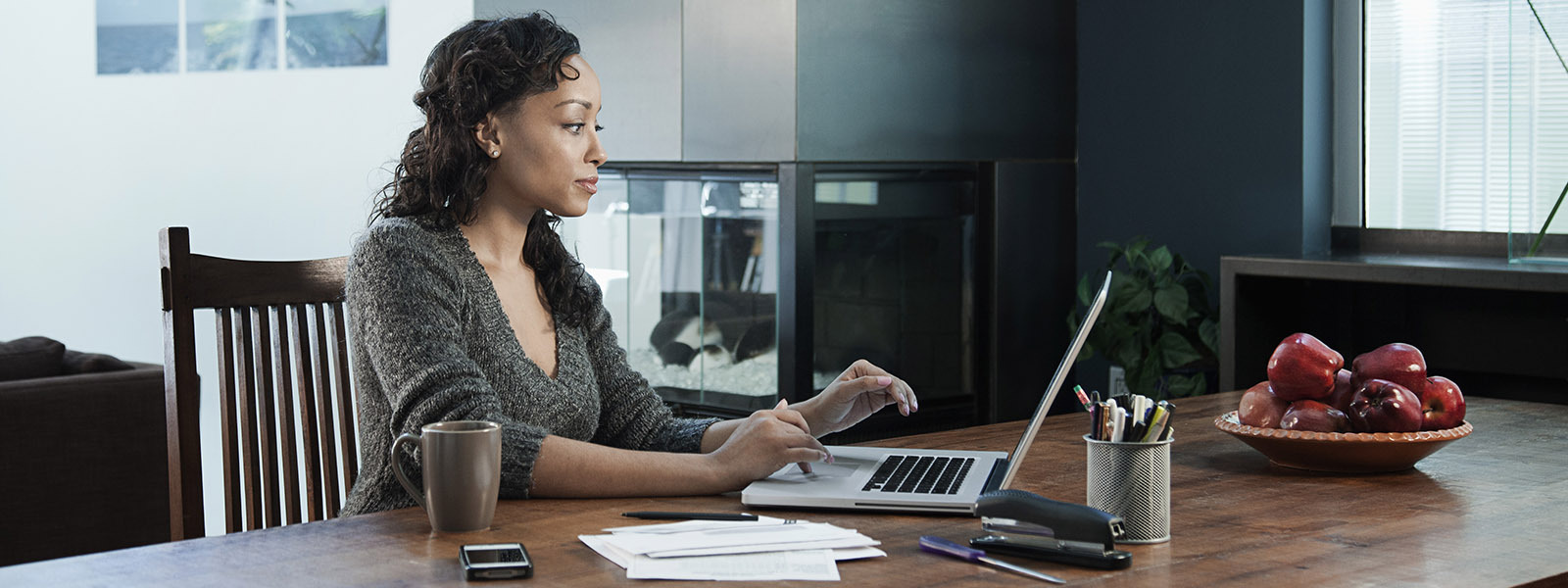 Woman using a laptop at a kitchen table