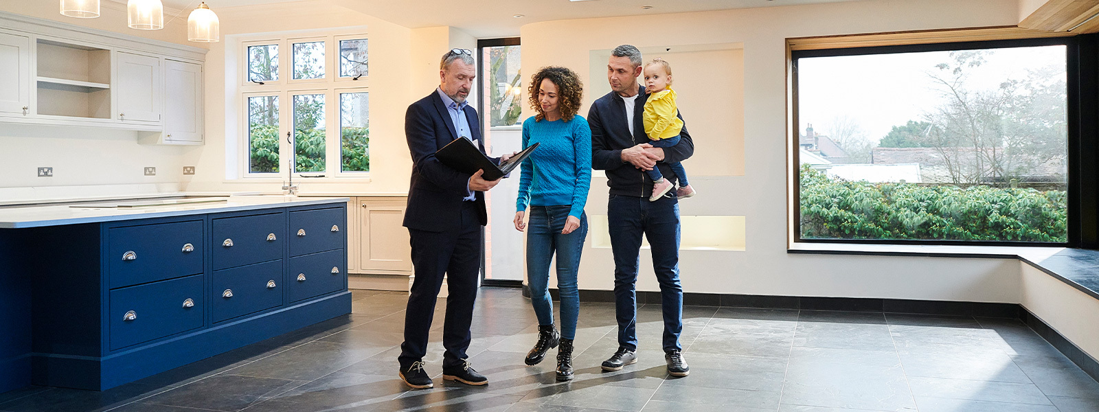 Real estate agent talking to a couple with a child at a home showing