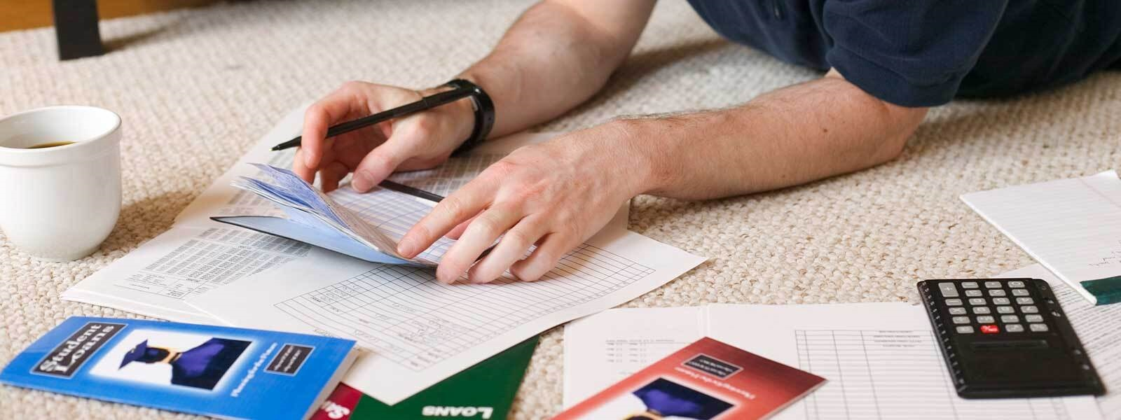 Man's hands holding a checkbook near a student loan pamphlet, scattered papers, and a calculator